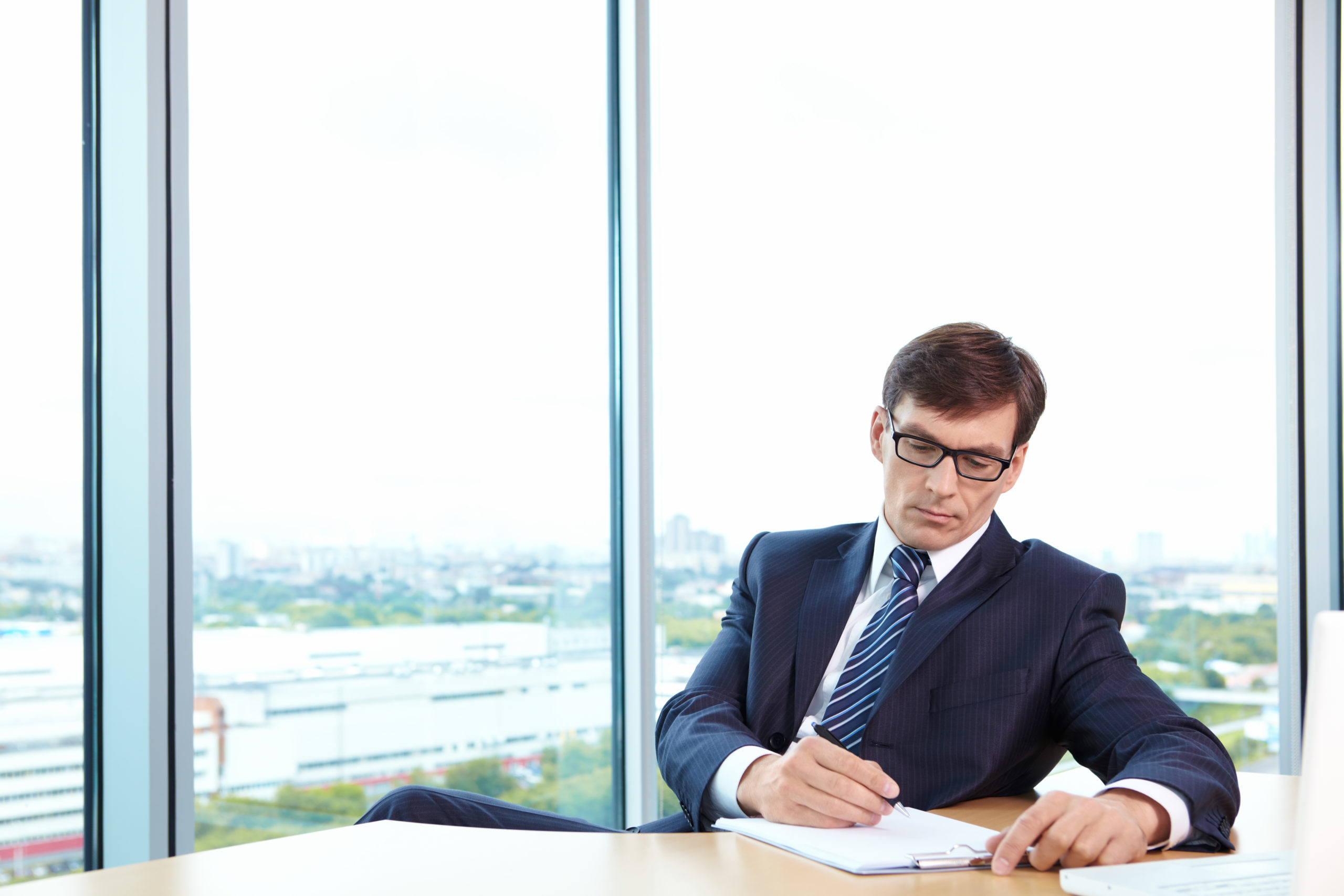 A man in business suit signs documents in the office
